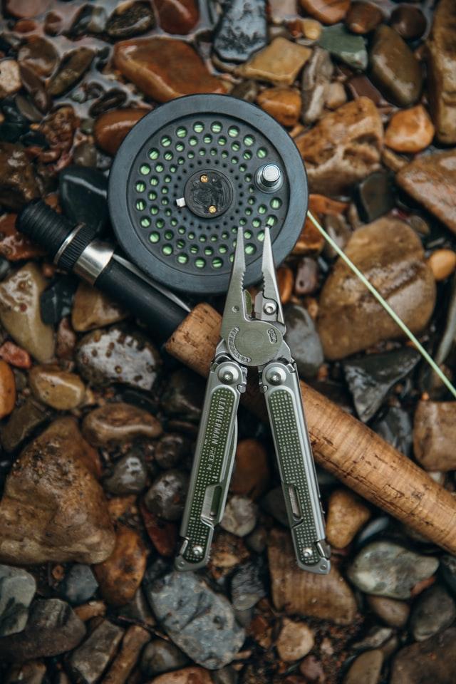Jaki multitool wybrać? Na zdjęciu mały multitool Leathermana położony na drewnianej wędce, na ziemi.