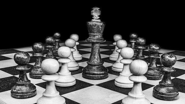 Szachy rozłożone na planszy z królem po środku, obraz czarno-biały. Szachy, jako prezent na dzień dziadka