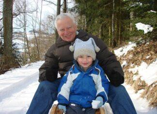 Dziadek z wnuczkiem na sankach w śnieżnej scenerii, tekst jak wybrać idealny prezent na dzień dziadka