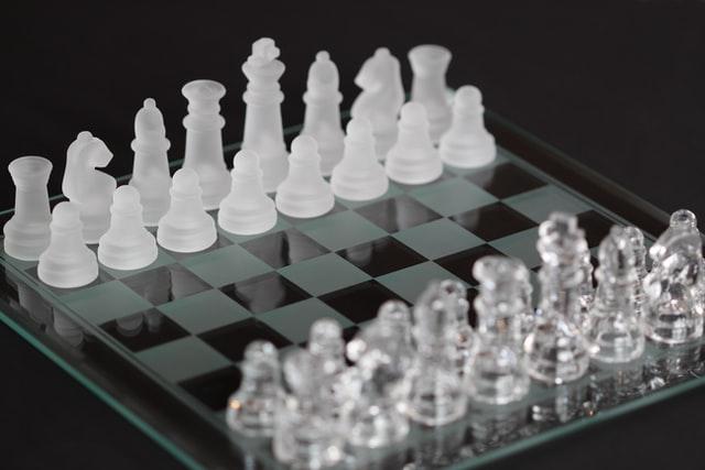 """Szklane szachy na prezent, na zdjęciu szachownica oraz szachy wykonane ze szła. """"Czarne"""" pionki i pola pokryte specjalną matową powłoką."""