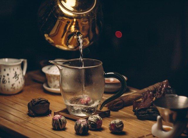 Jak parzyć herbatę kwitnącą? Najlepiej zalewać ją w szklanym imbryku. Na zdjęciu kulki herbaty kwitnącej, szklany imbryk do herbaty, w którym osoba parzy herbatę kwitnącą oraz w tle cukiernica i dzbanek na mleko