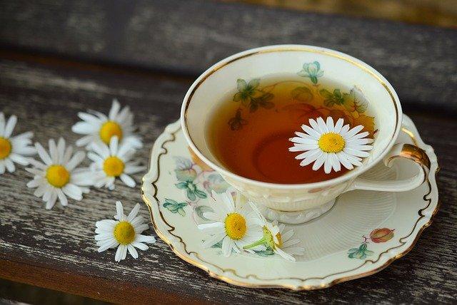 Herbata rumiankowa w ozdobnej, białej, porcelanowej, filiżance na ciemnym stole, w otoczeniu kwiatów rumianku. Herbata rumiankowa to jedna z łagodniejszych herbat ziołowych.