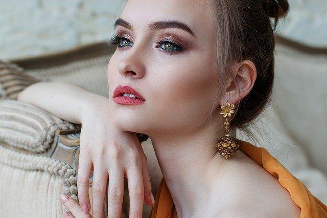 Czy makijaż może poprawić twój nastrój? Tak! Kobieta na zdjęciu wpatruje się w dal, siedzi oparta o sofę. NA twarzy ma subtelny makijaż.