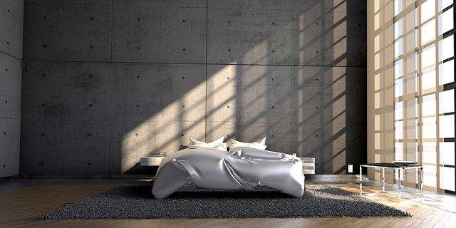Minilalizm charakteryzuje się prostotą zarówno na ścianach, jak i w meblach. NA zdjęciu minimalistyczna sypialnia w kolorach szarości - łóżko bez zagłówków oraz małe szafki nocne.