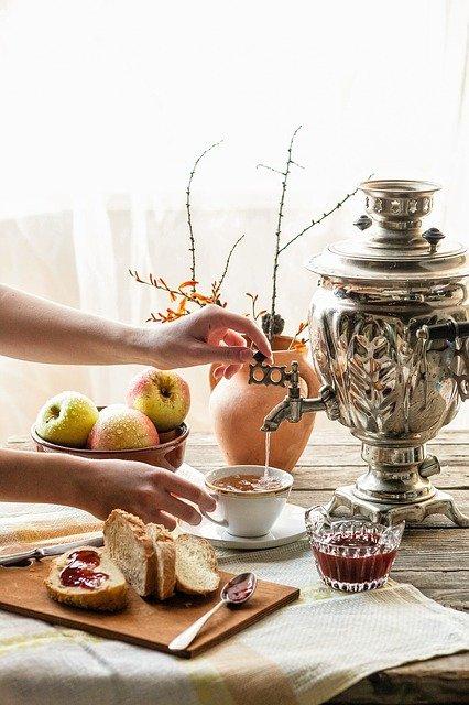 Imbryk do herbaty czy samowar? Na zdjęciu kobieta parzy herbatę z samowaru, obok rozłożone jest śniadanie.