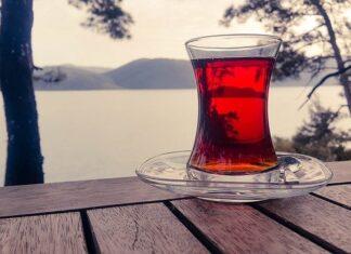 Herbata czerwona to utlenione liście herbaty chińskiej lub krzewu o nazwie rooibos. Oba napary mają bardzo intensywną czerwoną barwę i lekko karmelowy posmak. Na zdjęciu w szklance ukazany charakterystyczny kolor czerwonej herbaty na tle jeziora.