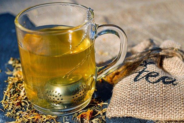 """Herbatę ziołową można parzyć bezpośrednio w szklance za pomocą specjalnego sitka do herbaty, który na łańcuszku wieszamy na wylewie. Na zdjęciu taka metoda parzenia herbaty. Wokół szklanki rozsypane są także płatki kwiatów oraz położony lniany woreczek z napisem """"tea"""" do przechowywania ziół."""