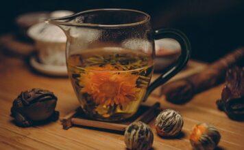 Szklany imbryk do herbaty, wraz z zaparzoną w nim kwitnąca herbata.