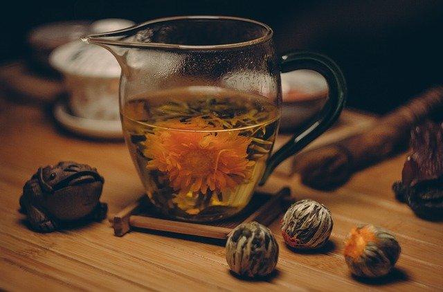 Szklany imbryk do herbaty, wraz z zaparzoną w nim kwitnącą herbatą. .