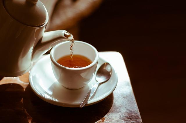 Zieloną herbatę najlepiej podawać w filiżankach, tak by móc delektować się jej smakiem. Na zdjęciu ktoś nalewa herbatę z imbryka porcelanowego do filiżanki stojącej na spodeczku, obok niej leży łyżeczka.