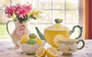 Białej herbaty nie warto pić z dodatkami, cytrusy oraz cukier mają zgubne działanie na dobroczynne jej włąściwosći. Na zdjęciu imbryk oraz filiżanka, a także misa na cytrusy. W tle wazon z kwiatami.