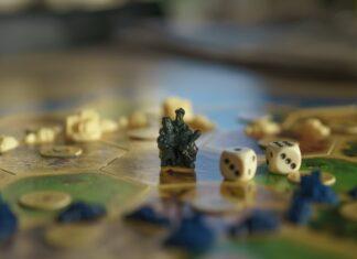 Jak wybrać grę planszową? Na zdjęciu rozłożona plansza do gry Osadnicy z Catanu - zbliżenie na złodzieja i pionki.