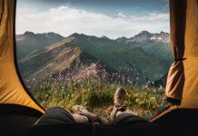 Co zabrać na kemping? Oto lista najpotrzebniejszych sprzętów. NA zdjęciu: mężczyzna leżący w namiocie, widać jego nogi, wejście do namiotu i niesamowity widok na góry.