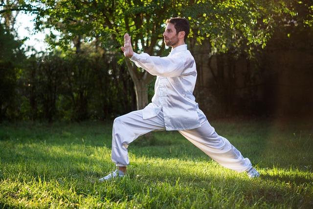 Jak zacząć ćwiczyć Tai Chi? To zdecydowanie prosta sprawa. Na zdjęciu mężczyzna w trakcie ćwiczeń w białym kimonie.