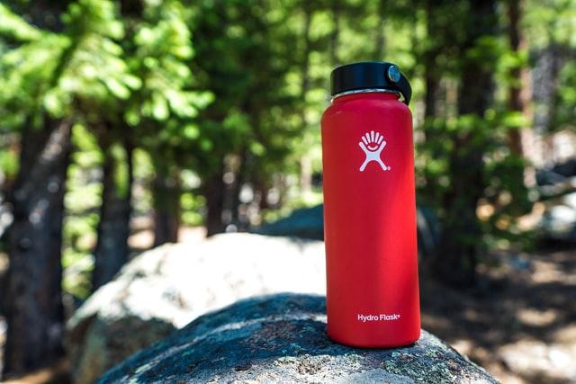 Butelki z filtrem świetnie sprawdzają się w terenie. NA zdjęciu czerwona metalowa butelka na wodę.