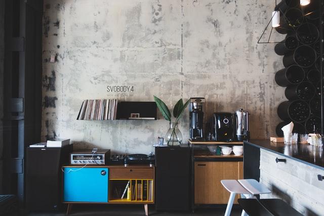 Styl industrialny idzie poznać na pierwszy rzut oka: betonowa ściana, meble z odzysku i metalowe elementy.