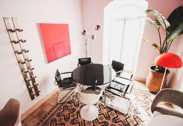 Styl eklektyczny lubi mieszać wzory i kolory: jadalnia, czarny okrągły stół i krzesła, drewniana podłoga, na ścienia ekstrawagancki czerwony obraz.