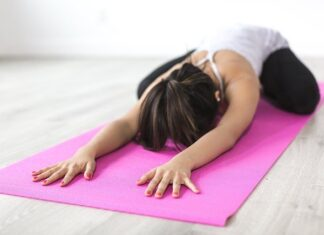 Dobrze dobrana mata do ćwiczeń będzie wsparciem dla naszego ciała. Na zdjeciu kobieta na macie.