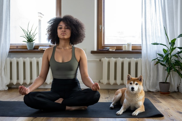 Kobieta medytująca na macie do ćwiczeń, obok pies. Wybierając matę do ćwiczeń wybierz taką, którą łatwo utrzymasz w czystości.