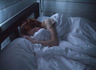 Higiena snu to budowanie nawyków, które ułatwią zasypianie i pozwolą nam sie wyspać. Na zdjęciu śpiąca kobieta.