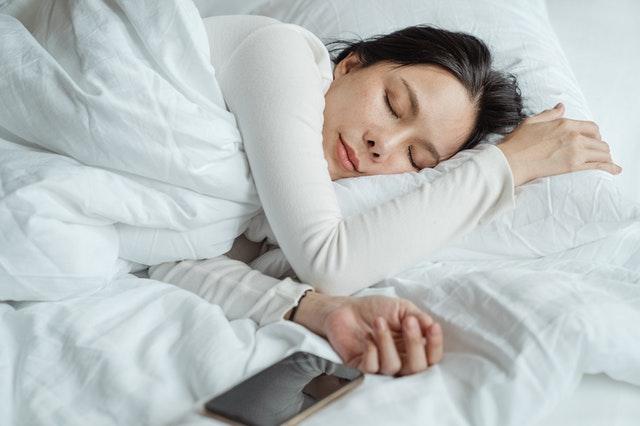 Korzystanie z telefonu tuż przed snem może pogorszyć jego jakość. Na zdjęciu kobieta śpiąca z telefonem w zasięgu ręki.