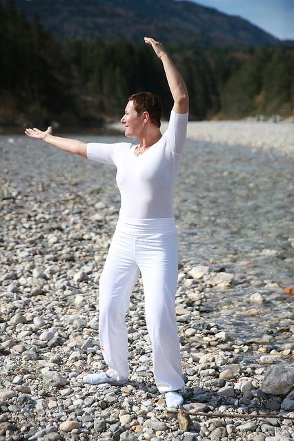 Każdy może ćwiczyć tai chi, niezależnie od wieku, płci i miejsca zamieszkania. NA zdjeciu kobieta ćwicząca tai chi nad rzeką.