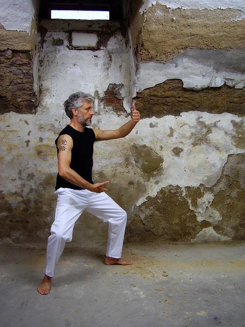 Do ćwiczenia Tai Chi nie potrzeba żadnego sprzętu, ani wyposażonego miejsca. Mężczyzna ćwiczy Tai chi w ruinach domu.