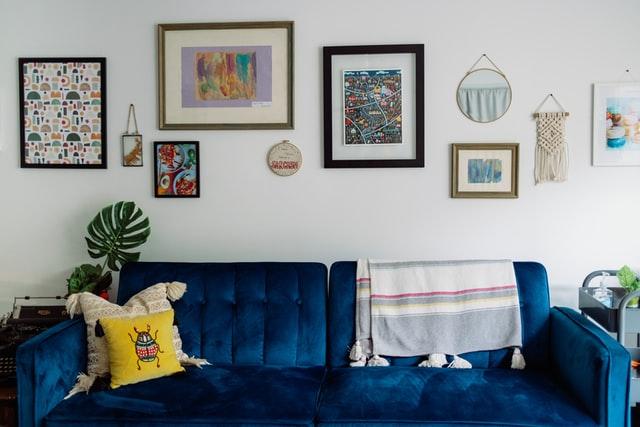Styl eklektyczny to mieszanina wszystkiego po trochu - na zdjęciu krzykliwa, granatowa sofa, stare zdjecia na ścianie i żółte poduszki.