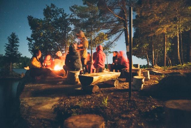 Osoby siedzące przy ognisku w lesie