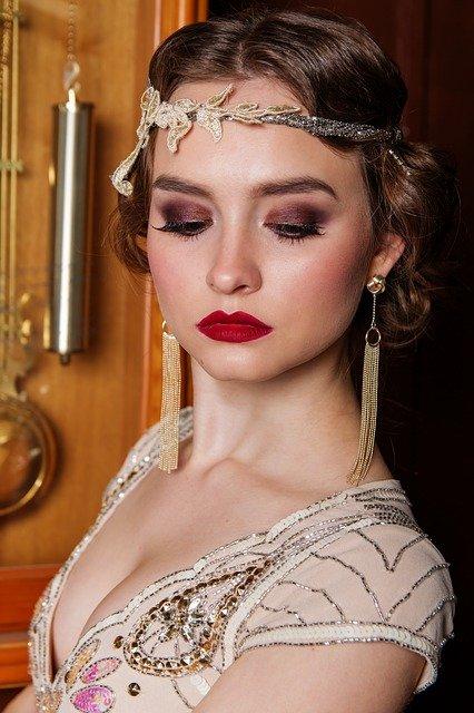 Trendy makijażu wieczorowego w 2021 roku wyznacza między innymi nostalgia za starymi czasami, dlatego wszelkie odniesienia do poprzednich epok są mile widziane. Na zdjęciu kobieta wystylizowana na lata 20. XX wieku.