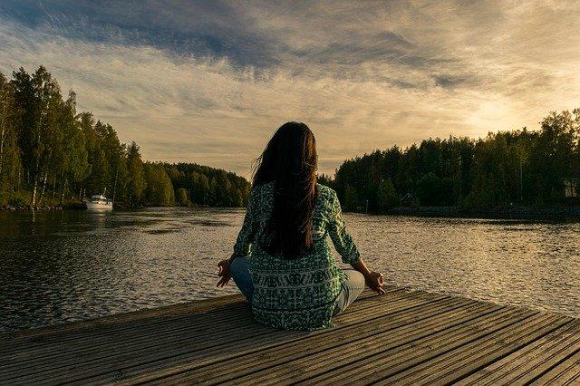 Jak zacząć medytować? Możesz zacząć w każdym miejscu i o każdej porze. Tak jak kobieta na zdjęciu medytująca na molo nad jeziorem.