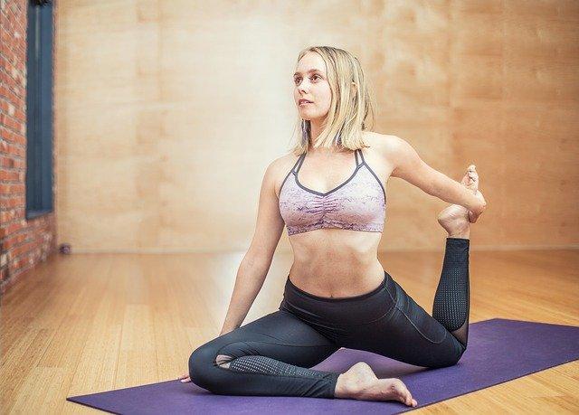Jak zacząć ćwiczyć jogę w domu? Nie jest to wcale trudne! Kobieta na macie do jogi wykonuje jedną z pozycji.